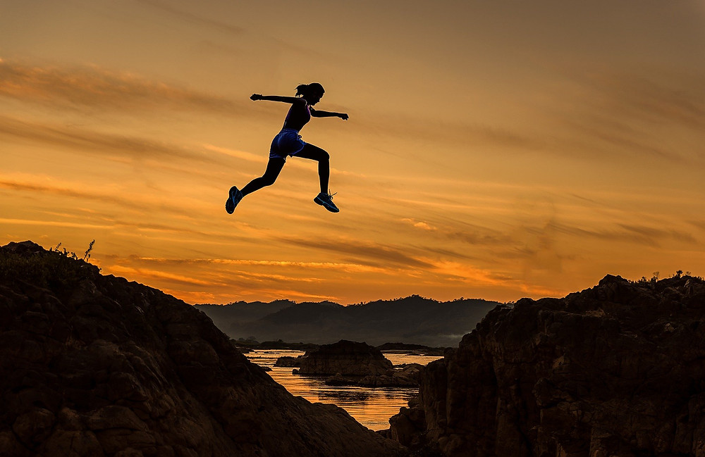Silhouette of person leaping from hill to hill showing courage