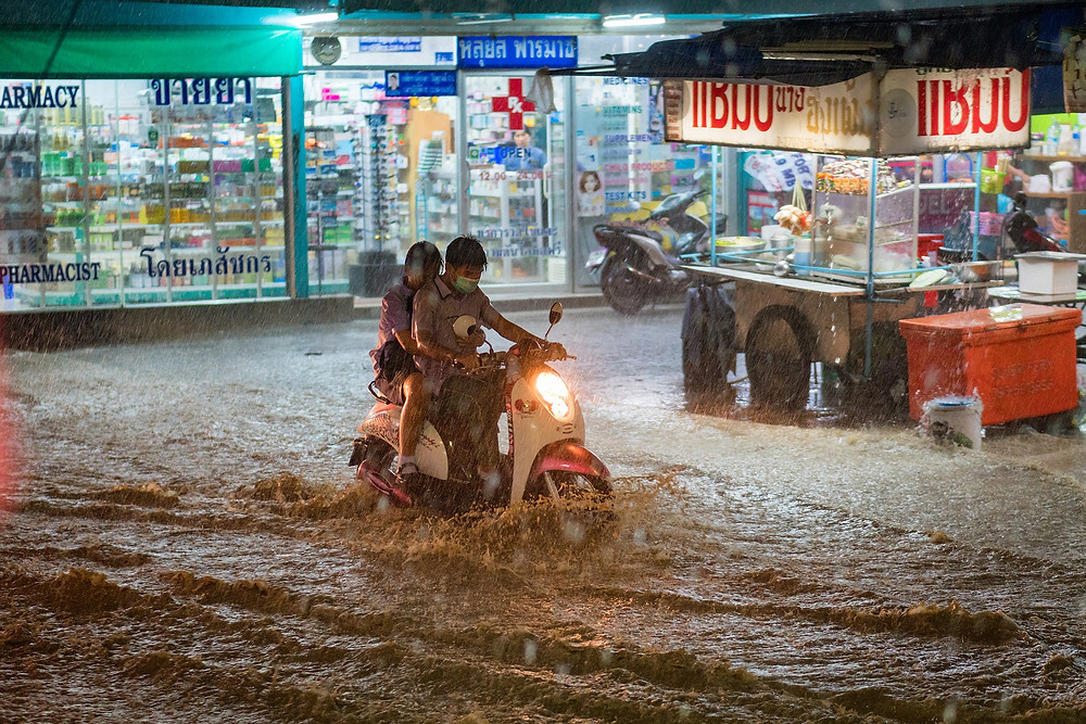 Couple driving moped through unexpected flood