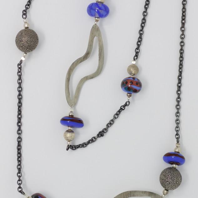 """Grand sautoir """"maillechort et violines"""", éléments découpés et martelés : """"formes molles"""" en maillechort, perle ronde en argent, perle violettes, bordeaux et pervanche, verre sodocalcique."""