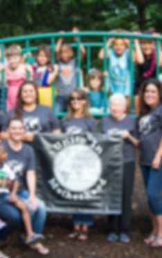 A group photo of mothers and their children at the park. They are holding the Unite In Motherhood banner.