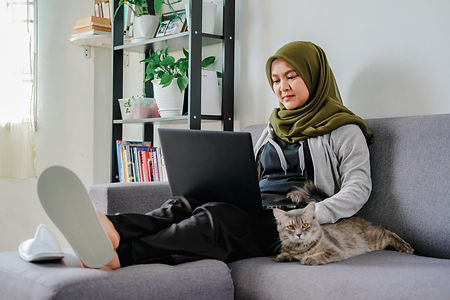 Young happy asian muslim female adult sitting at the sofa, working from home due to lockdo