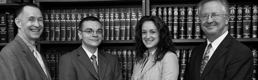 Sharpnack Bigley Stroh & Washburn attorneys standing in front of a shelf filled with law books.