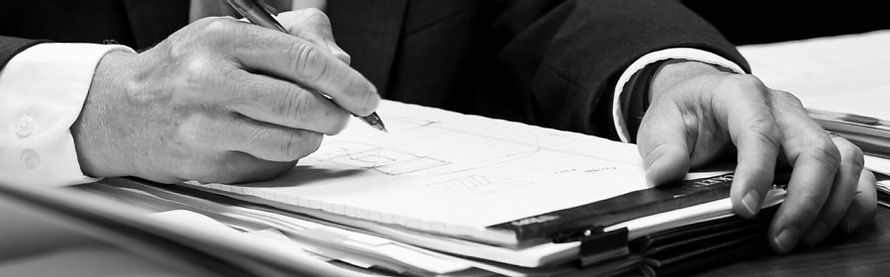 Close-up image of person holding a pen and starting to write on a legal pad.