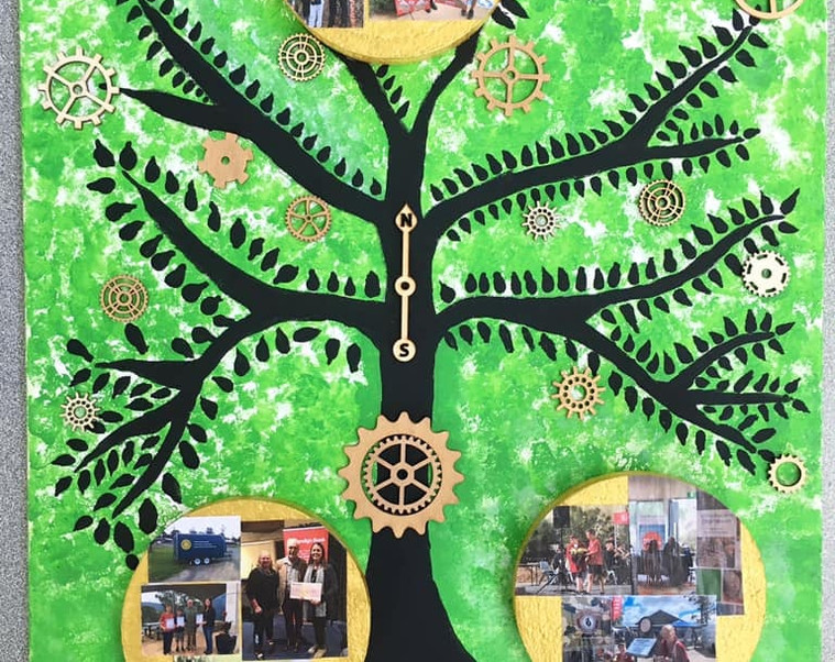 """What community means to us? Our mural was created by the students of Strathewen Primary school and it represents the connection we have with our community. The design is of a tree of life with photos that show the community support given to our school. The cogs on the picture represents the connection between our school and community groups and how they engage with each other and work together to encourage and support the growth and development of our students. The Rotary clubs have provided us with the opportunity to have a fairy garden, pizza oven, bike trailer and to be part of the local Kinglake market. We have had the honour to have our students speak at the R.S.L. Anzac Day service in Diamond Creek. We have received funds from the Bendigo bank for a large-scale concert event involving many local schools. There has been community involvement in both centenary events and anniversaries as well as funding for our highly successful Strathewen and Arthurs Creek Bushfire Education Partnership. The support and encouragement of these community groups enables our school to offer our students a wide range of opportunities. """"It takes a village to raise a child"""" (African proverb) #diamondcreekmuralfestival"""