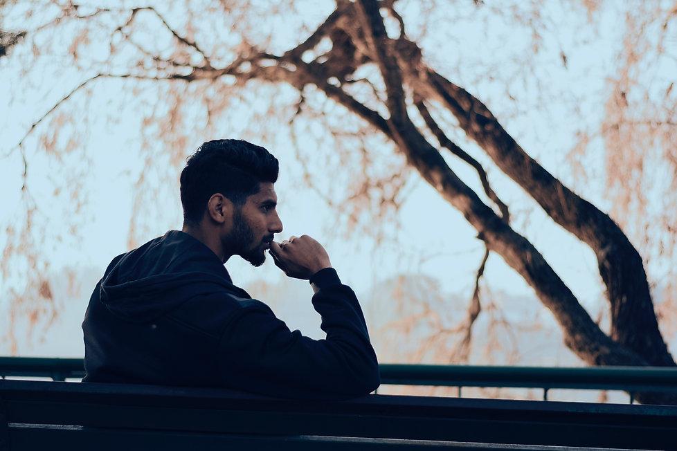 man-in-black-hoodie-sitting-on-bench-nea