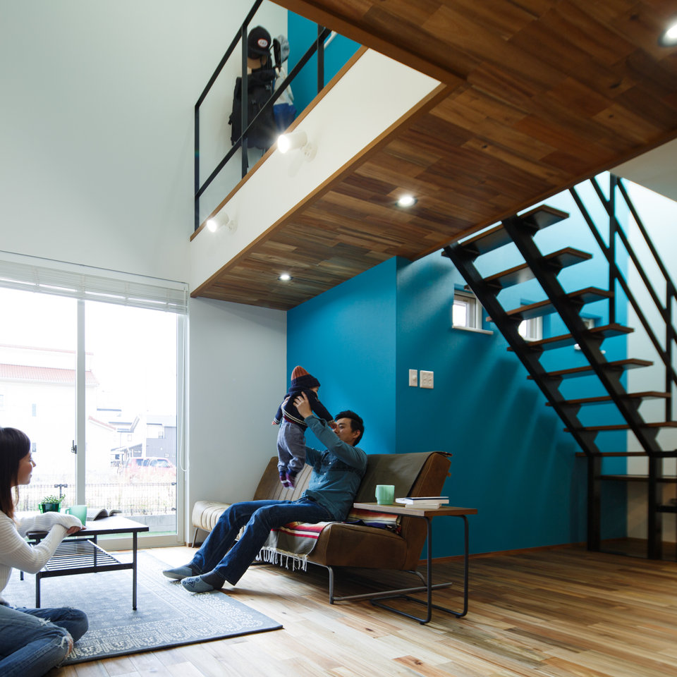 リビングのアクセントに2階まで続く明るい青い壁。