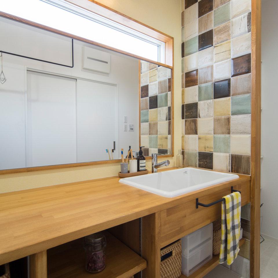 センスの良い洗面台のタイルと大きな鏡は奥様のこだわり