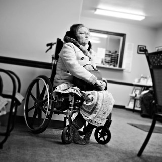 More from a series on grief and distress centered around waiting rooms. The frown that the buttons on her coat and her purse strap make almost mirror the frown on her face.
