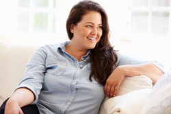 Portrait Of Overweight Woman Sitting On Sofa.jpg