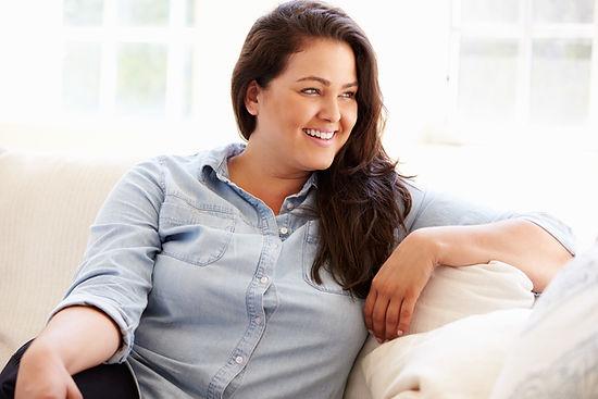 Portrait Of Overweight Woman Sitting On Sofa.jpg