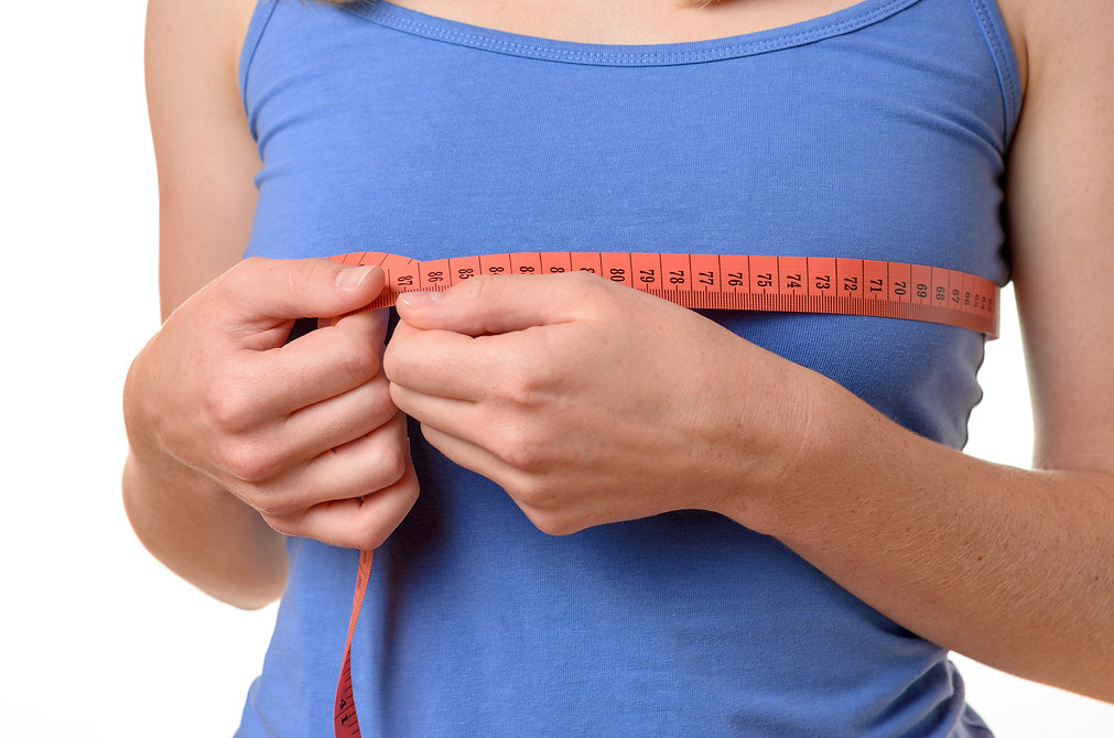 Young Woman Measuring Her Breasts.jpg
