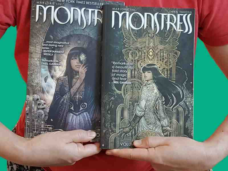 Model holds Volumes 1 & 2 of Monstress graphic novel side by side