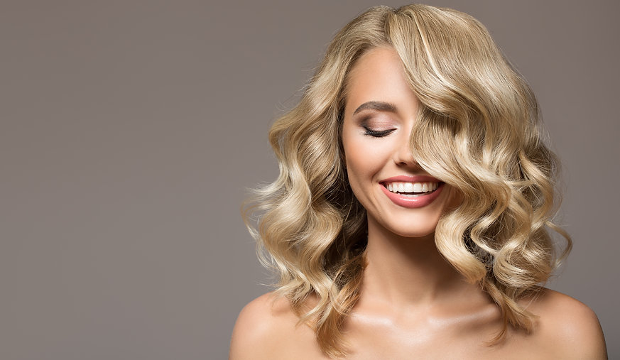 Blonde woman with curly beautiful hair smiling on gray background. .jpg