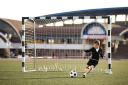 boy-plays-football-on-stadium-PXB44TT.jp