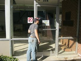 "(image description: a white masculine person with jeans and a short sleeve t-shirt looks into an empty storefront through a glass door. She is wearing a blue hat and next to the hat is a sticker with a ""no guns"" image)"