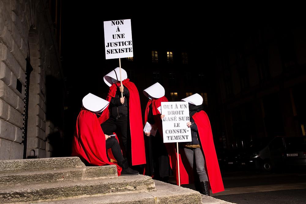 """servantes écarlates sur les marches de l'Hôtel de ville à Neuchâtel. Elles tiennent deux panneaux """"non à une justice sexiste"""" et l'autre """"oui à une droit basé sur le consentement"""""""