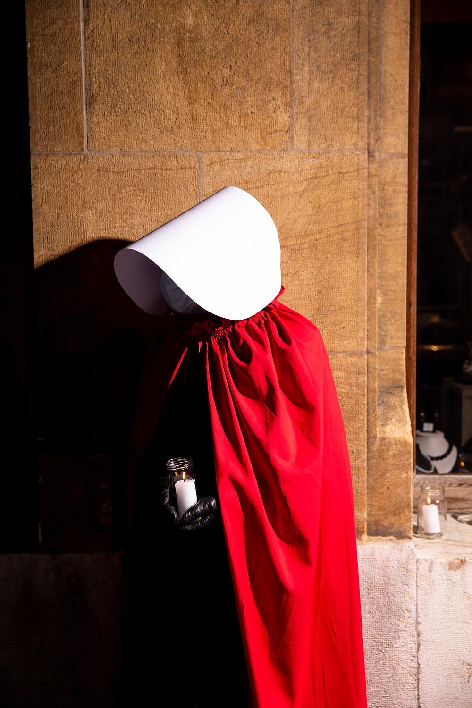 une servante écarlate habillée en rouge, avec une coiffe blanche tient une bougie allumée.