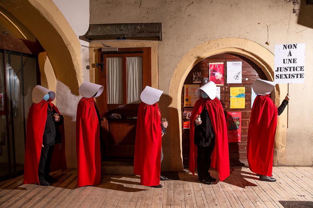 """5 servantes écarlates alignées contre un mur au centre ville de Neuchâtel. Celle de droite tient le panneau """"non à une justice sexiste"""""""