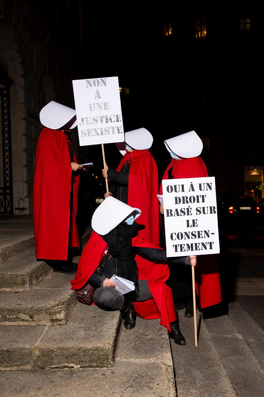 """4 servantes écarlates sur les marches de l'Hôtel de ville à Neuchâtel. Elles tiennent deux panneaux """"non à une justice sexiste"""" et l'autre """"oui à une droit basé sur le consentement"""". photo verticale"""