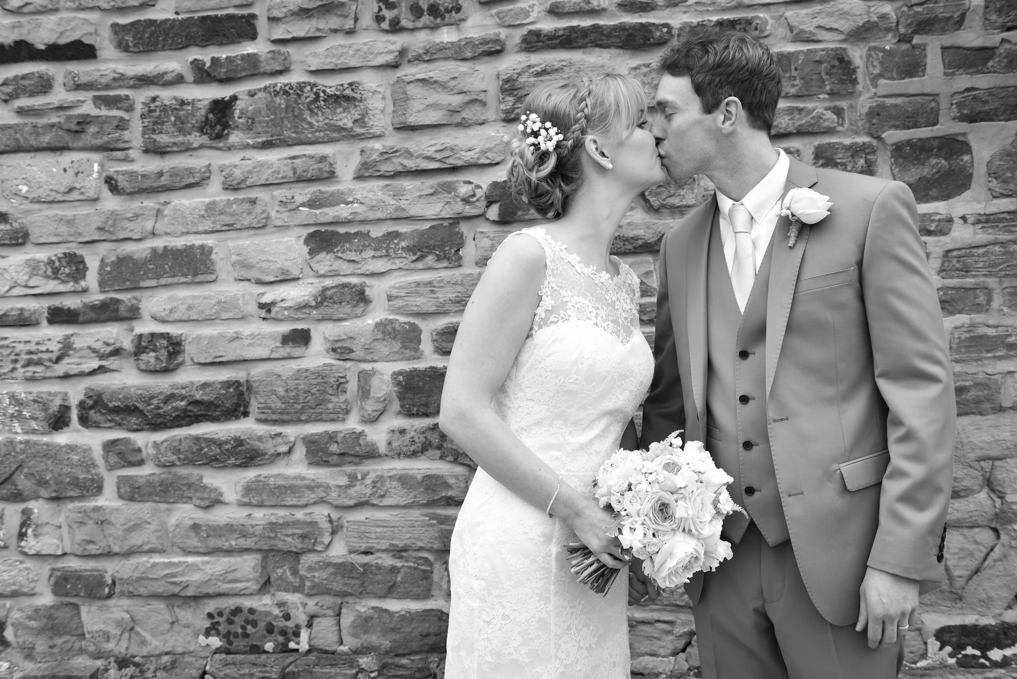 Wedding kiss by a brick wall