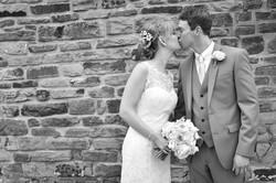 Wedding kiss by a brick wall