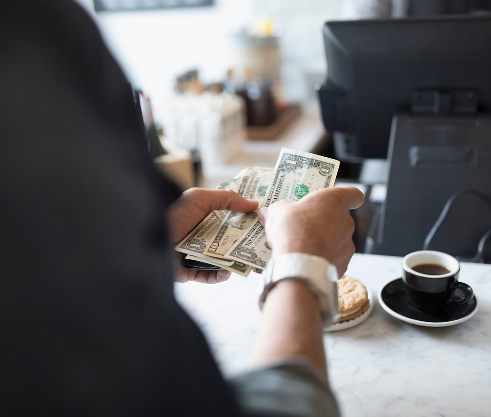 customer-paying-with-cash-at-cafe-counte