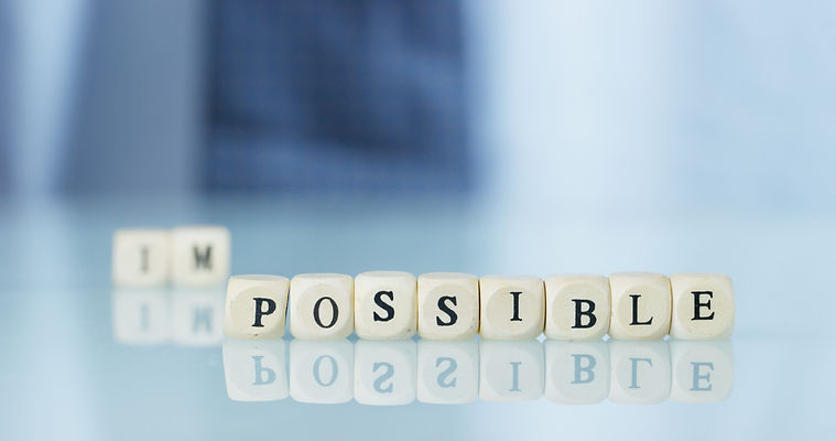 "A hand turns the word ""Impossible"" to ""P"