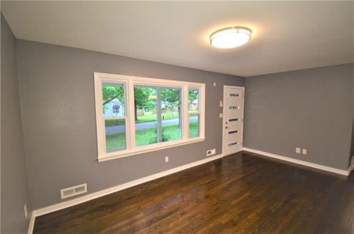 6108 Northern Ave., Raytown, MO 64133 - Home For Sale - living room with restored hardwood floors and stylish front door