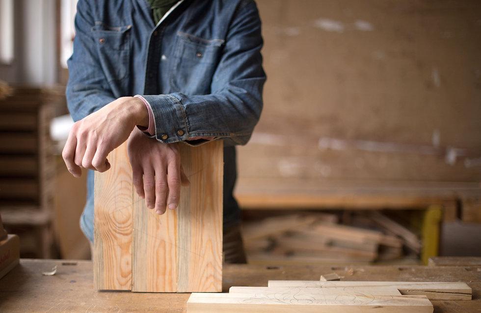 Schreiner stützt sich auf Holzstück
