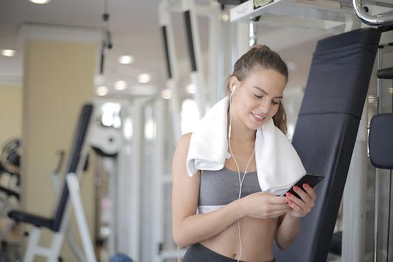 joyful-sporty-female-in-earphones-browsi