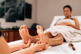 enjoying-foot-massage-treatment-in-a-wel