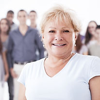 A senior woman smiling and standing in f