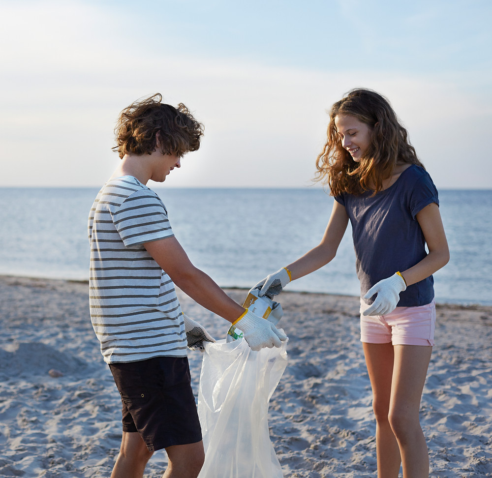 A boy and girl teenager work together clearing litter from a beach.