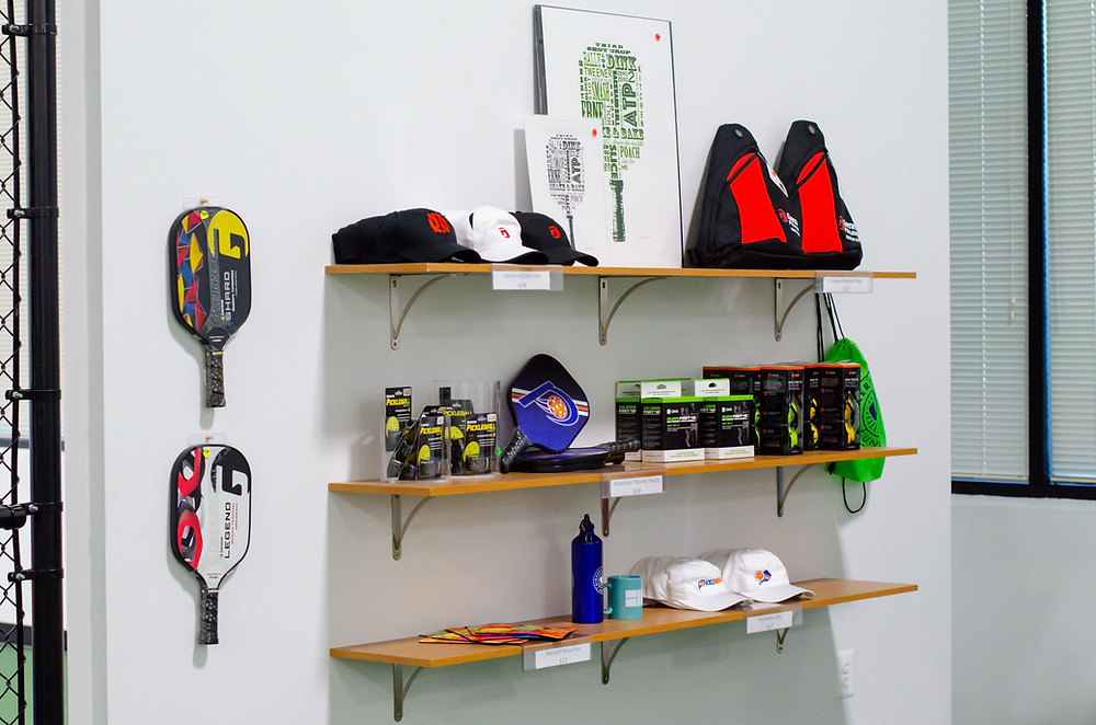 three shelves along a wall hold various pickleball equipment such as paddles, balls, hats, bags, and even artwork