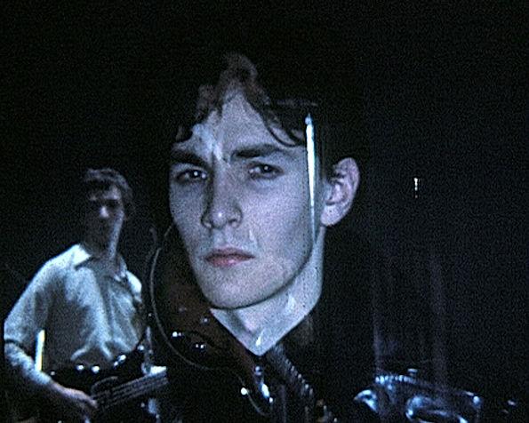 Image extraite d'un film de Georges Rey Triptyque. Portrait d'un garçon avec à côté de lui un guitariste. Portrait brouillé par la surimpression.