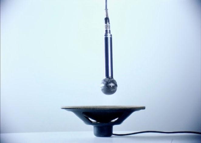 Image extraite du film Microfilm de Georges Rey. Un microphone est suspendu au dessus d'un haut parleur duquel part un fil.