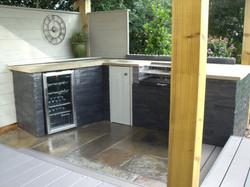 slate tiled, wooden worktops in outdoor kitchen