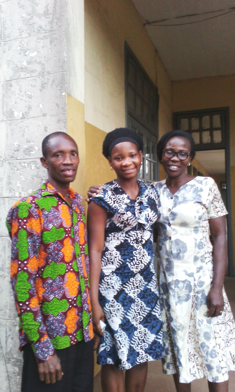 Emmanuel, Victoria and Sister Rose standing on stairs to school dressed in Ghanaian clothing. The Deaf Dream sponsors scholarships for Deaf college students in developing nations. Carol MacNicholl, Destiny Yarbro, Sanne Winsser board of directors.