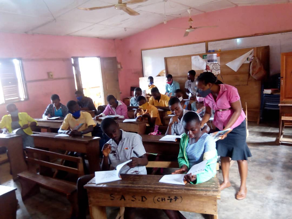 Victoria Aggrey is in her classroom with students sitting at small desks, reading from the books, some with facemasks on. Victoria is in a pink blouse and grey skirt, leaning over to help one of her students. The classroom has pink walls, a couple of fans, a white board, and cement floors.