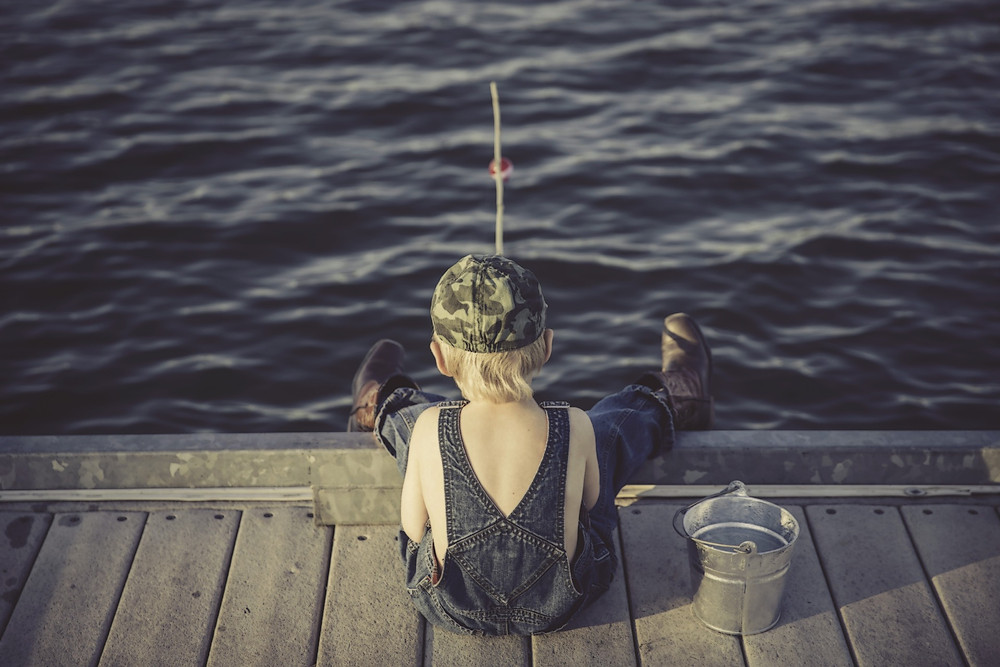 "Boy sitting on dock with fishing pole. Simplicity = Happiness. Destiny Yarbro blog. ""Simplicity is extremely important for happiness."""