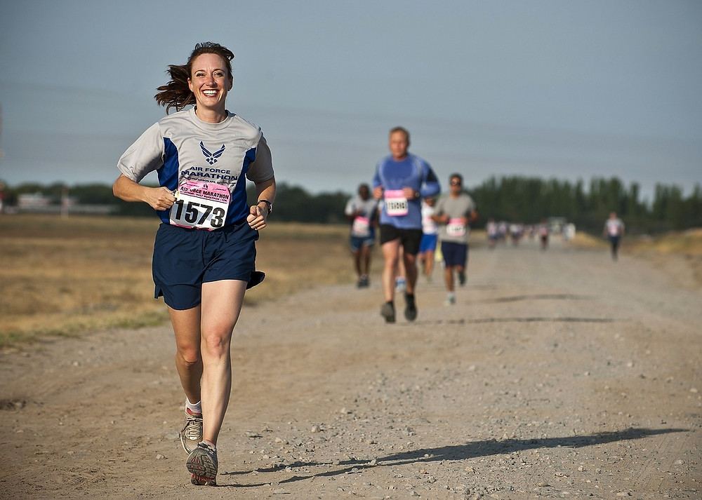 Woman runs on a dirt road in the air force marathon with large smile. The Power of Finish Lines: My 3 Step System to Setting Goals. Destiny Yarbro blog.