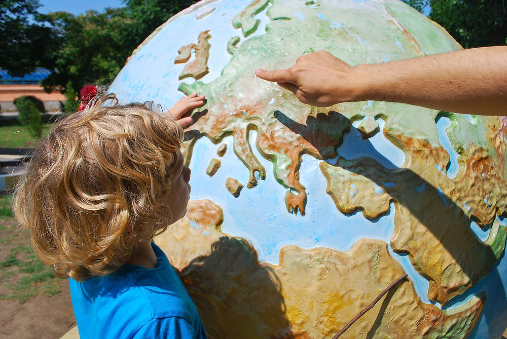 Child standing by a large globe of the world with parent teaching them where Europe is.