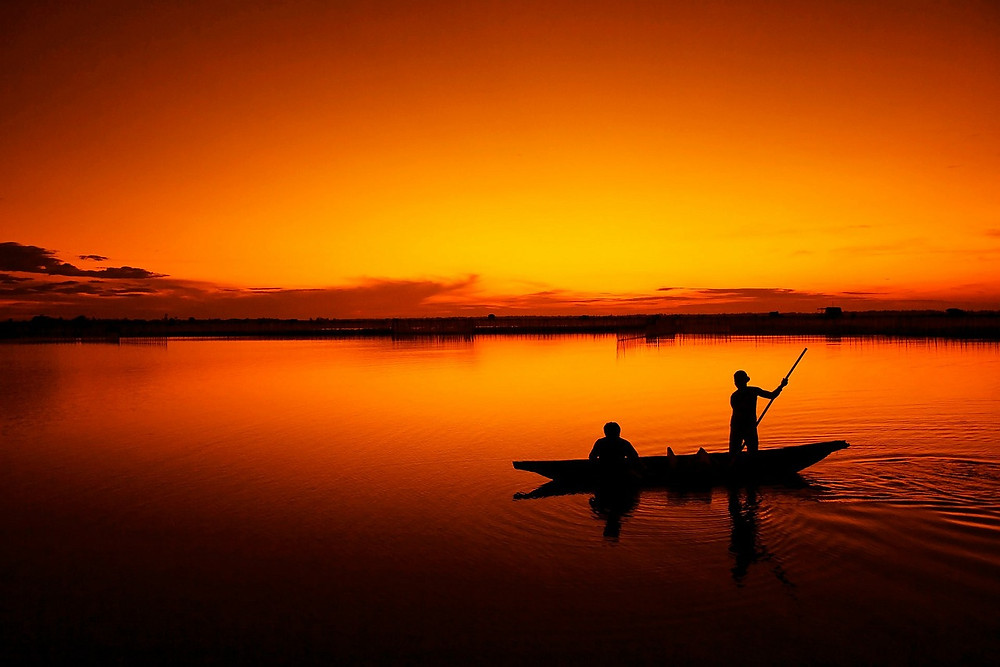 "Two people fishing on river during orange/red sunset. Simplicity = Happiness. Destiny Yarbro blog. ""Simplicity is extremely important for happiness."""