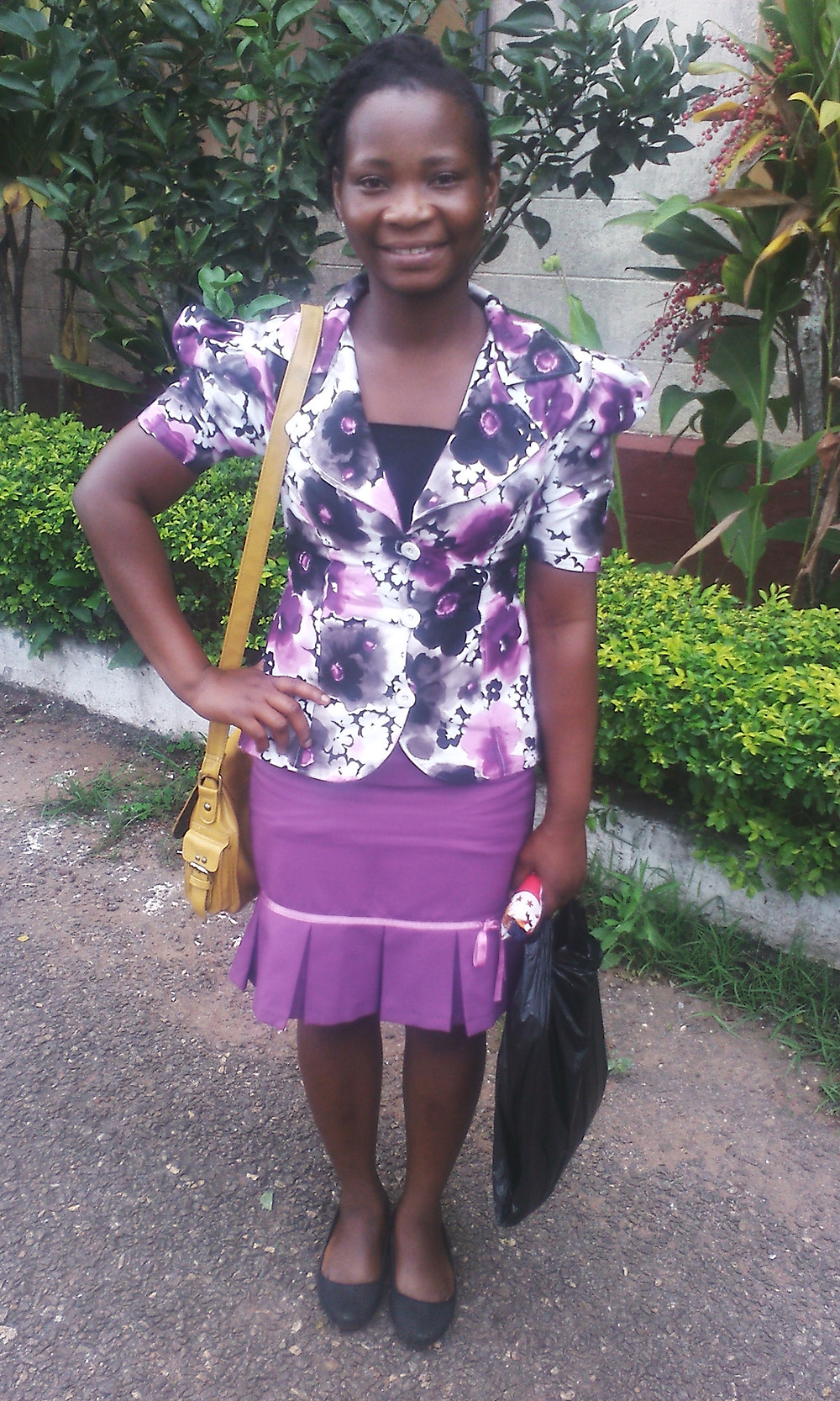 Photo of Victoria Aggrey - dressed in suit with purple flower print, classy hairstyle, and smiling. She is standing with hand on hip and with bags in font of green foliage behind her. The Deaf Dream sponsors scholarships for Deaf college students in developing nations. Carol MacNicholl, Destiny Yarbro, Sanne Winsser board of directors.