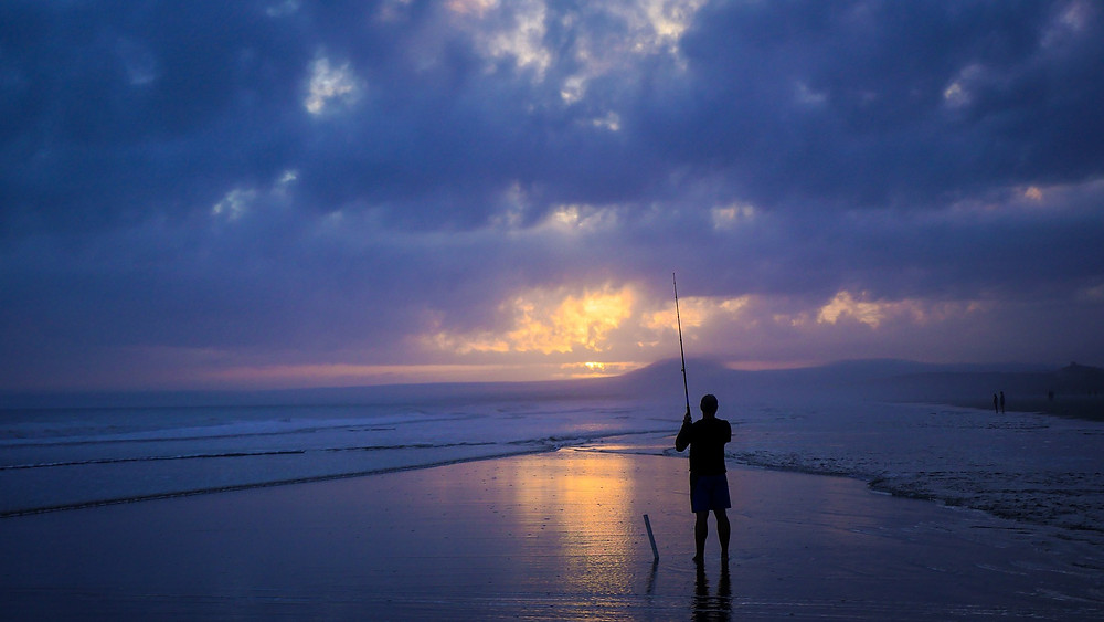 "Man standing with fishing pole on the ocean beach with beautiful purple and dark blue clouds. Simplicity = Happiness. Destiny Yarbro blog. ""Simplicity is extremely important for happiness."""