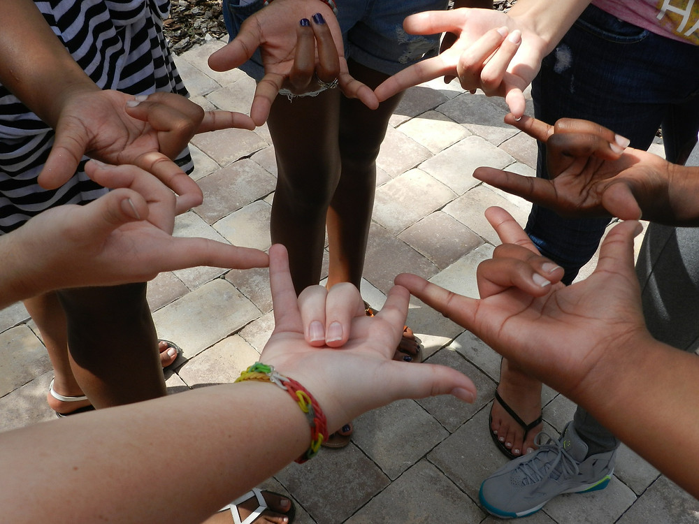 """People standing in a circle each putting their hands in the center of the circle with the """"I Love You"""" hand sign."""