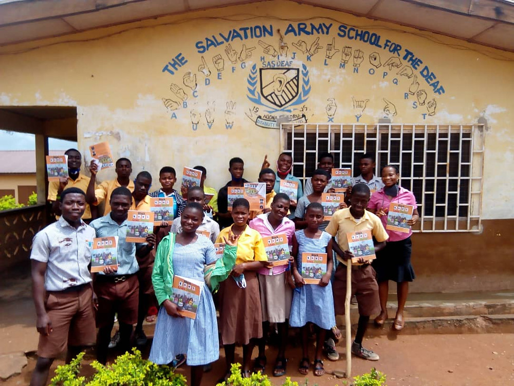 About 20 Deaf students in school uniforms are holding Dr. Lissa's book in front of their school: The Salvation Army School for the Deaf (written in fingerspelled letters)