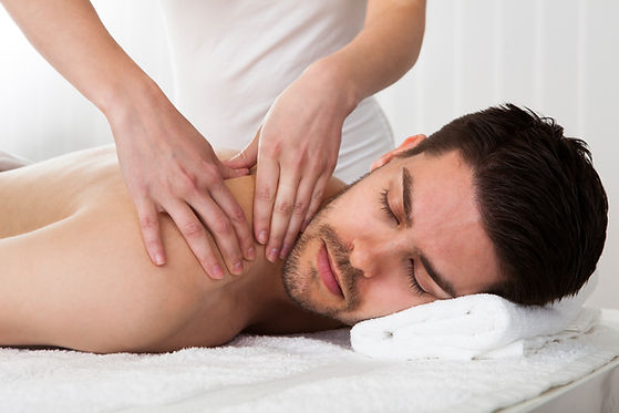 A relaxed man being massaged by therapist