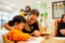 Educator helping a toddler with artwork at Watsonia Early Learning Centre