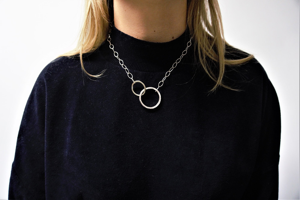 Two silver circles, one gold and one silver. Interlinking, hanging from an oval link fine silver chain. The necklace is 9ct gold and sterling silver.
